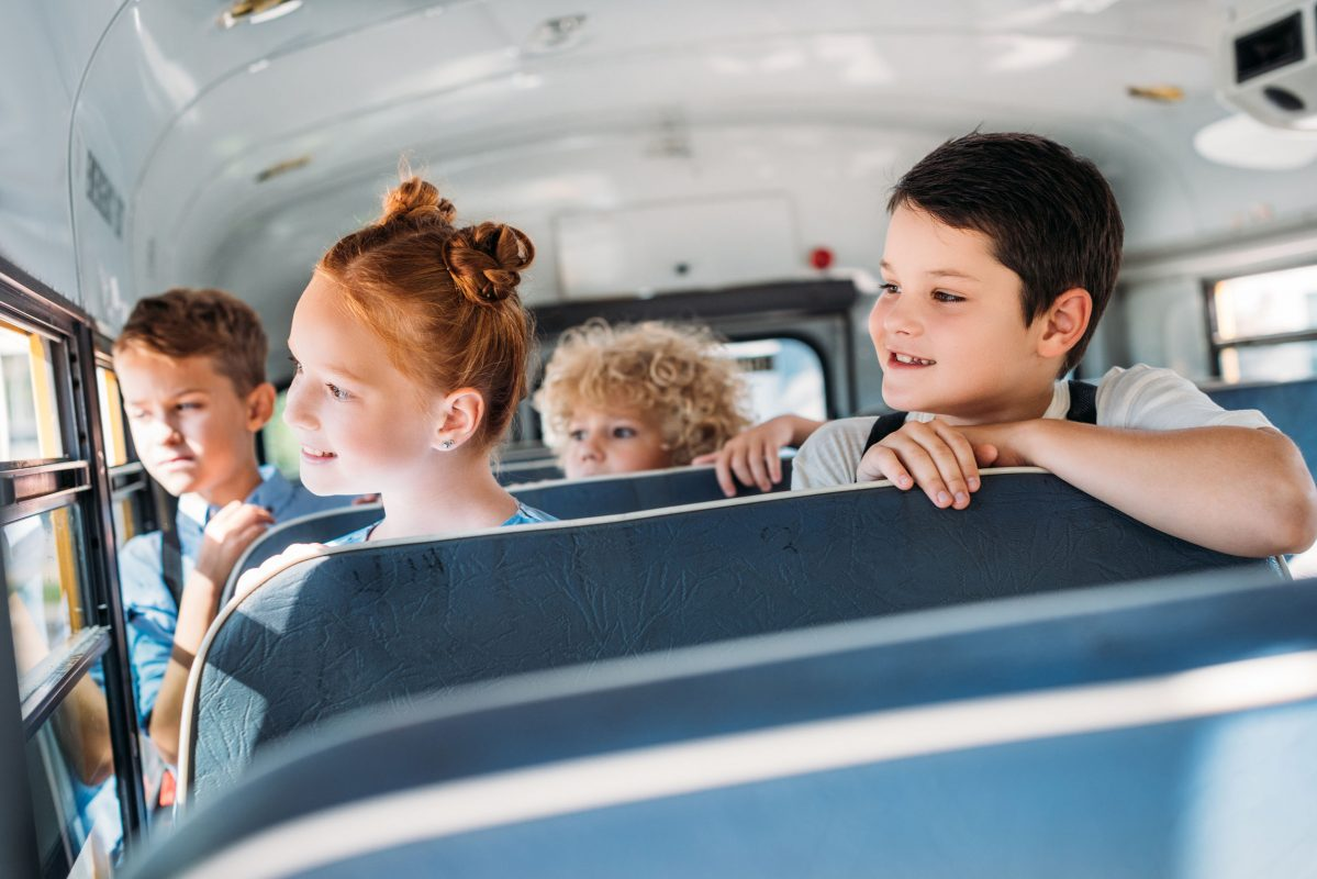 group of pupils riding on school bus and looking through window